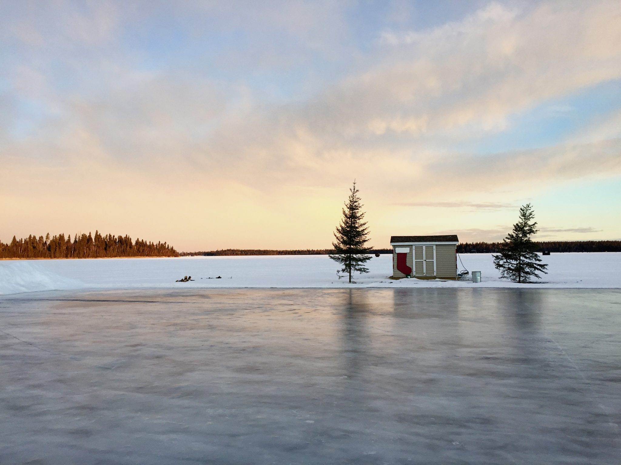 lovely sunset at Emma Lake in winter at Sunset bay on frozen pond by ice shack